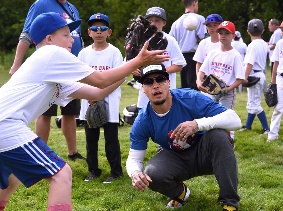 Chicago Cubs infielder Javier Baez runs through tagging drills with kids during his one-day baseball camp Monday at Elk Grove High School.