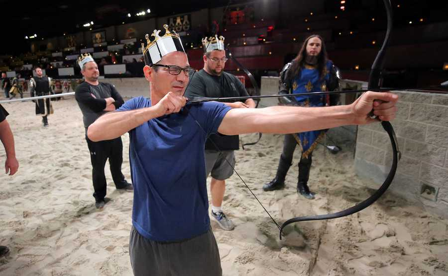 "Chris Montenero, of Hoffman Estates shoots a bow and arrow as about two dozen Chicago-area fathers participated in ""Fiercest Fathers"" at Medieval Times in Schaumburg Thursday."