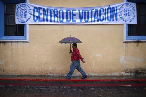 A man walks in the rain to a polling station during general elections in Antigua, Guatemala, Sunday, June 16, 2019. Voters are choosing between 19 candidates for a four-year presidential term that begins in Jan. 2020. The winner needs an absolute majority, making an August runoff between the two top vote-getters likely.