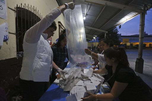 Election officials start counting votes after polling stations closed during general elections in Guatemala City, Sunday, June 16, 2019. Voters are choosing between 19 candidates for a four-year presidential term that begins in Jan. 2020. The winner needs an absolute majority, making an August runoff between the two top vote-getters likely.