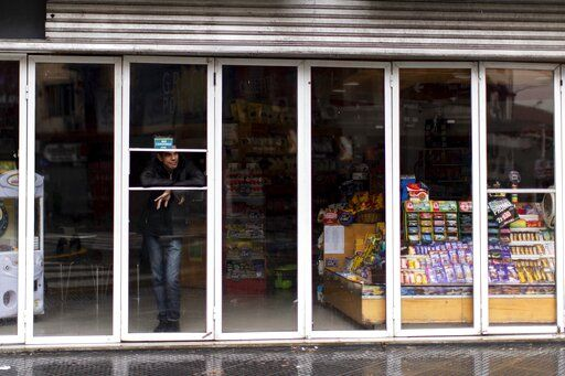 A man stands inside a store without power during a blackout, in Buenos Aires, Argentina, Sunday, June 16, 2019. Argentina and Uruguay were working frantically to return power on Sunday, after a massive power failure left large swaths of the South American countries in the dark.