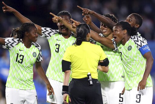 Nigerian players points towards the electronic screen as they protest a yellow card and a penalty awarded against their goalkeeper Chiamaka Nnadozie by referee Melissa Borjas of Honduras, center, during the Women's World Cup Group A soccer match between Nigeria and France at the Roazhon Park in Rennes, France, Monday, June 17, 2019.
