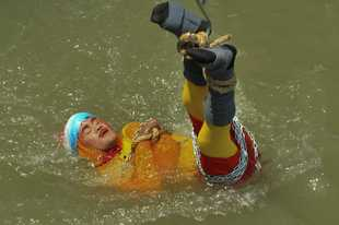 This Sunday, June 16, 2019 photograph shows Indian magician Chanchal Lahiri, being lowered in Hooghly river during a live performance in Kolkata, India. According to eye witnesses, the 40- year old stuntman drowned while trying to perform an underwater escape act.
