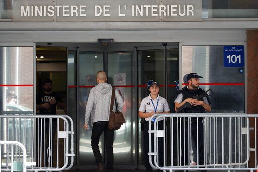 Police officers guard the Anti-Corruption Office of the Judicial Police headquarters in Nanterre, outside Paris,Tuesday, June 18, 2019. Former UEFA president Michel Platini has been arrested in relation to a corruption probe into the awarding of the 2022 World Cup to Qatar, a judicial official said Tuesday.