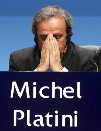 FILE - In this Tuesday, March 24, 2015 file photo UEFA President Michel Platini covers his face during a news conference at the end of the 39th Ordinary UEFA Congress in Vienna, Austria. Former UEFA president Michel Platini has been arrested Tuesday June 18, 2019 over the awarding of the 2022 World Cup.