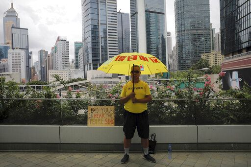 A man holds an umbrella outside the Legislative Council following last weekend's massive protest against the unpopular extradition bill in Hong Kong, Tuesday, June 18, 2019. Hong Kong's government headquarters reopened Tuesday as the number of protesters outside dwindled to a few dozen and life returned to normal in the former British colony.