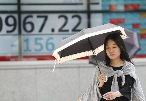A woman walks by an electronic stock board of a securities firm in Tokyo, Tuesday, June 18, 2019. Stocks in Asia mostly advanced Tuesday ahead of interest rate decisions by the U.S. Federal Reserve and other central banks.