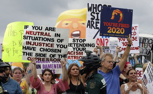 Protestors hold up anti President Donald Trump signs during a rally Tuesday, June 18, 2019, in Orlando, Fla. A large group of protestors were holding a rally near where Trump was announcing his re-election campaign.
