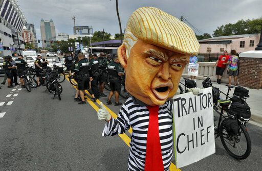 A protestor wearing a large President Donald Trump head walks near law enforcement officers during a rally Tuesday, June 18, 2019, in Orlando, Fla. A large of protestors were holding a rally near where Trump was announcing his re-election campaign.
