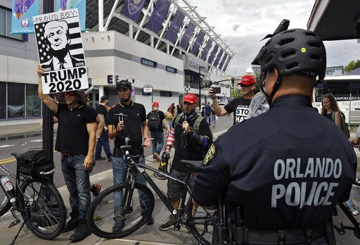 An Orlando, Fla., police officer keeps an eye on a group of President Donald Trump supporters as they shout at protestors Tuesday, June 18, 2019, in Orlando.