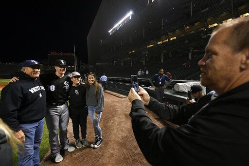 Chicago White Sox pitcher Zack Collins poses for photos with friends and family after the White Sox defeated the Chicago Cubs 3-1 during a baseball game Tuesday, June 18, 2019, at Wrigley Field in Chicago.