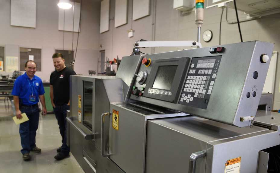 Elgin Community College's Industrial Manufacturing Program received a seven-axis Swiss CNC machine from Swiss Automation in Barrington on Wednesday. ECC instructor Umberto Tinajero and Marc Moran, Swiss Automation vice president of operations, are pictured in the background.