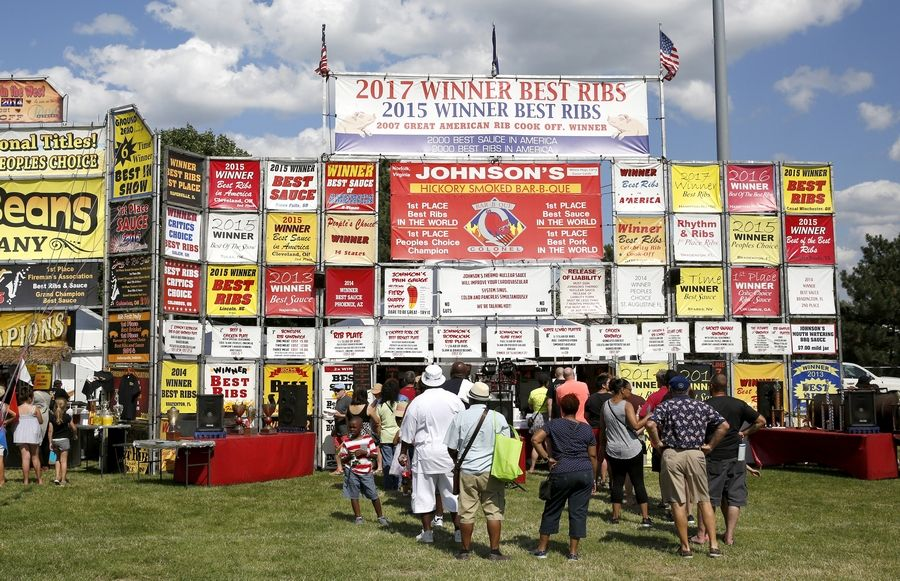 Patrons wait in line to purchase Johnson's Hickory Smoked Bar B-Que during a previous Ribfest in Naperville.