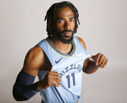 FILE - In this Sept. 24, 2018, file photo, Memphis Grizzlies guard Mike Conley poses during the team's NBA basketball media day  in Memphis, Tenn. A person with knowledge of the decision says the Memphis Grizzlies have traded veteran point guard Mike Conley, who has played the most games in franchise history, to the Utah Jazz. The person says the Grizzlies swapped Conley for Jae Crowder, Kyle Korver and Grayson Allen. The person spoke to The Associated Press Wednesday, June 19, 2019, on condition of anonymity because neither Memphis nor Utah has announced the trade.