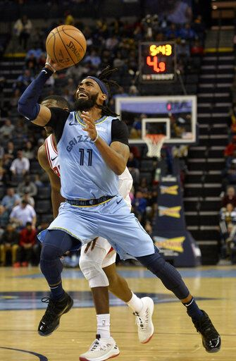 FILE - In this Feb. 27, 2019, file photo, Memphis Grizzlies guard Mike Conley (11) shoots the ball in the first half of an NBA basketball game against the Chicago Bulls, in Memphis, Tenn. A person with knowledge of the decision says the Memphis Grizzlies have traded veteran point guard Mike Conley, who has played the most games in franchise history, to the Utah Jazz. The person says the Grizzlies swapped Conley for Jae Crowder, Kyle Korver and Grayson Allen. The person spoke to The Associated Press Wednesday, June 19, 2019, on condition of anonymity because neither Memphis nor Utah has announced the trade.