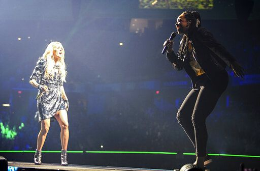 "In this Sunday, June 16, 2019, photo, Carrie Underwood, left, performs ""The Champion"" with Indiana Fever's Erica McCall onstage during Underwood's concert in Indianapolis. McCall, who said she started rapping in high school and had the nickname Medium E, auditioned for the guest spot at the urgings of team vice president Tamika Catchings. (Jessica Hoffman/Indiana Fever via AP)"