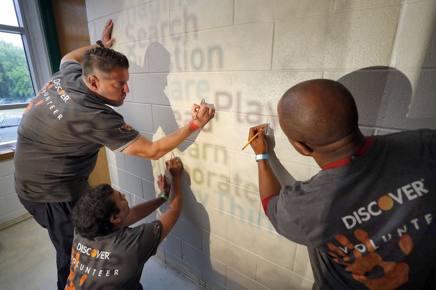 From left, Roland Krocin of Wheeling, Nilesh Bhatpalliwar of Arlington Heights and Paul Saweh of Wauconda trace letters for a mural Thursday at Gavin South Middle School in Ingleside.