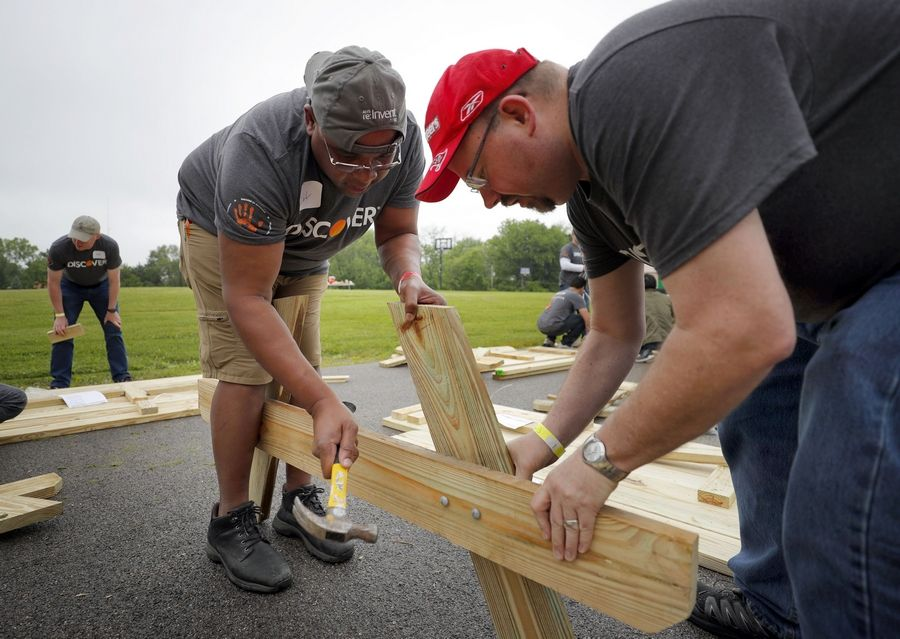 Will Hinton of Prospect Heights, left, and Tom Rogers of Mount Prospect build a picnic bench Thursday at Gavin South Middle School in Ingleside.