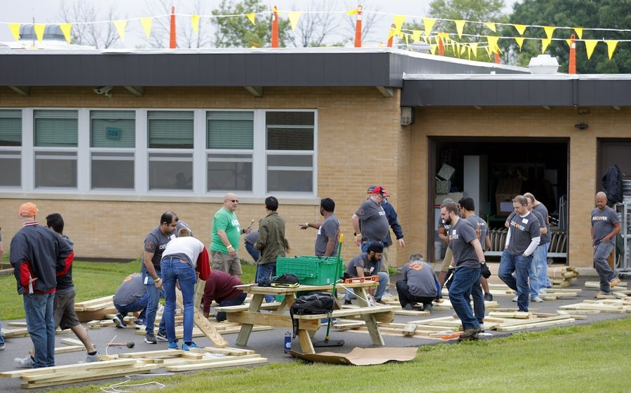 Picnic benches are assembled Thursday as nearly 500 volunteers from Discover Financial Services visited Gavin South Middle School in Ingleside to give the school an indoor and outdoor makeover.