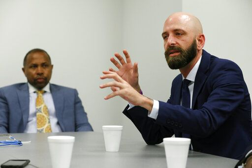 In this Wednesday, June 19, 2019 photo, attorney Troy Pradia, left, listens as Eric Ridenhour describes the moment after a crane collapsed on the building and the apartment that he and his fiancee Kiersten Smith lived in, during an interview in Dallas.