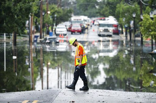 A utility worker walks the edge of the floodwaters submerging Broadway in Westville, N.J. Thursday, June 20, 2019. Severe storms containing heavy rains and strong winds spurred flooding across southern New Jersey, disrupting travel and damaging some property.