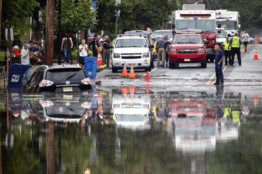 Officials and residents gather on the edge of the floodwaters submerging Broadway in Westville, N.J. Thursday, June 20, 2019. Severe storms containing heavy rains and strong winds spurred flooding across southern New Jersey, disrupting travel and damaging some property.
