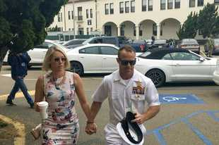 Navy Special Operations Chief Edward Gallagher, right, walks with his wife, Andrea Gallagher as they arrive to military court on Naval Base San Diego, Tuesday, June 18, 2019, in San Diego. Jury selection continued Tuesday morning in the court-martial of the decorated Navy SEAL, who is accused of stabbing to death a wounded teenage Islamic State prisoner and wounding two civilians in Iraq in 2017. He has pleaded not guilty to murder and attempted murder, charges that carry a potential life sentence. (AP Photo/Julie Watson)