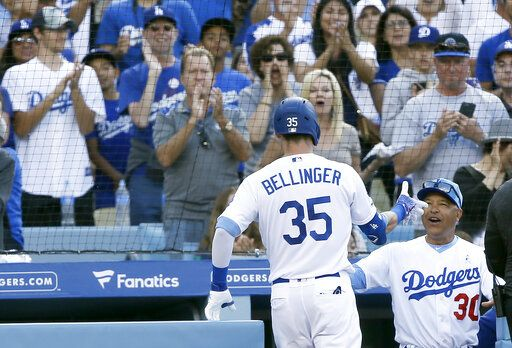 Los Angeles Dodgers' Cody Bellinger gets congratulations from manager Dave Roberts, right, after Bellinger hits a solo home run against the Chicago Cubs during the sixth inning of a baseball game in Los Angeles, Sunday, June 16, 2019.