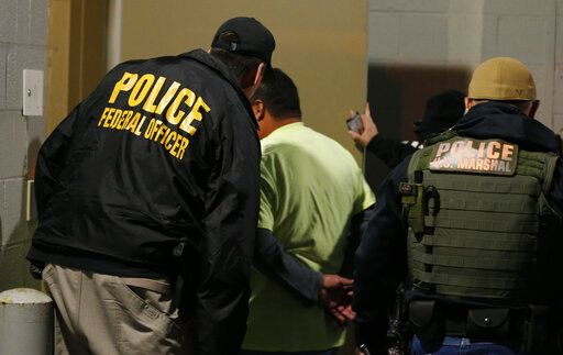 FILE - In this Oct. 22, 2018, file photo U.S. Immigration and Customs Enforcement agents escort a target to lockup during a raid in Richmond, Va. Carrying out President Donald Trump's hard-line immigration policies has exposed ICE to unprecedented public scrutiny and criticism, even though officers say they're doing largely the same job they did before the election, prioritizing criminals.