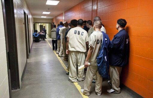 FILE - In this Sept. 29, 2011 photo, inmates at the Cook County Jail in Chicago, the second largest county jail in the nation, line up to be processed for release. Cook County Commissioners have passed an ordinance this month that orders the jail not to hold illegal immigrants until Immigration and Customs Enforcement, ICE officers can pick them up.