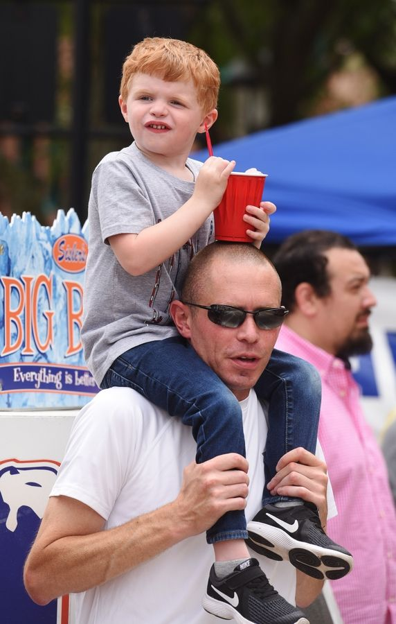 Nick Sanderson, 4½, of St. Charles, rests his icy drink on his dad Rob's head Sunday while watching the 70th annual Swedish Days parade in Geneva.