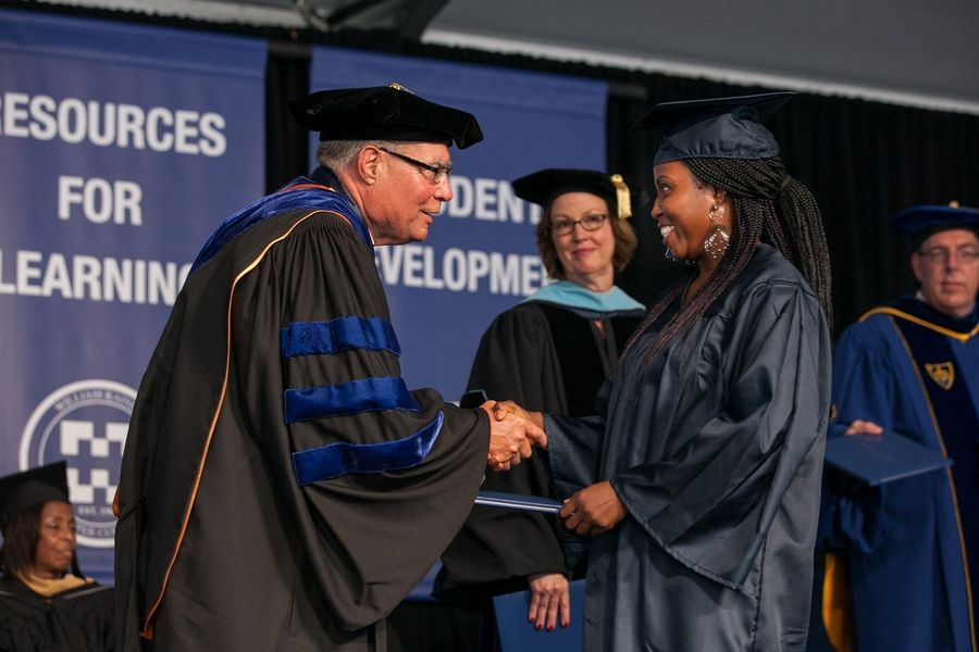 Harper College President Ken Ender hands a diploma to a graduate at the college's 2015 commencement ceremony. During Ender's decadelong tenure, the college's graduation rate climbed from 13.9% to 32.7%.