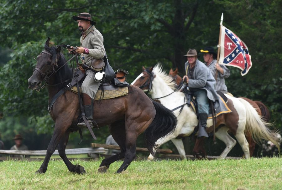 Confederate cavalry members ride into position as they engage Union troops while portraying the Battle of Vicksburg during Civil War Days at Lakewood Forest Preserve near Wauconda.
