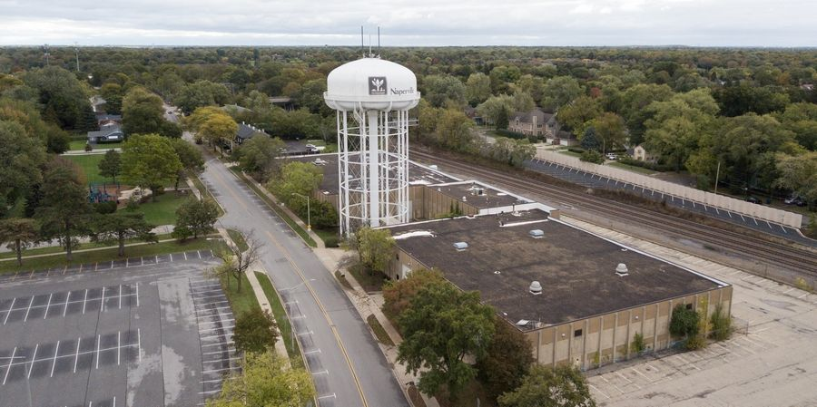 Naperville plans to demolish a former public works building near this water tower and replace it with 263 more daily-fee parking spaces for commuters. But the spots will be temporary.