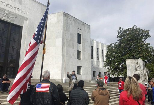 "In this photo taken Sunday, June 23, 2019, a small crowd of local Republicans show their support of a Republican walkout outside the Oregon State Capitol in Salem, Ore. The gathering took place only a day after the Senate President ordered the statehouse to close over a ""possible militia threat,"" the latest escalation in a Republican walkout over proposed climate policy that has put Democrats' top legislative priorities at risk."