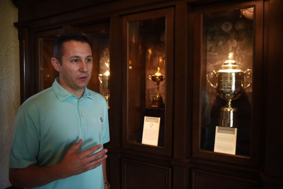 "Vince Pellegrino, the tournament director for the BMW Championship, shows a display of replica trophies at Medinah County Club. ""This is one of the most iconic clubhouses in American golf,"" he said."