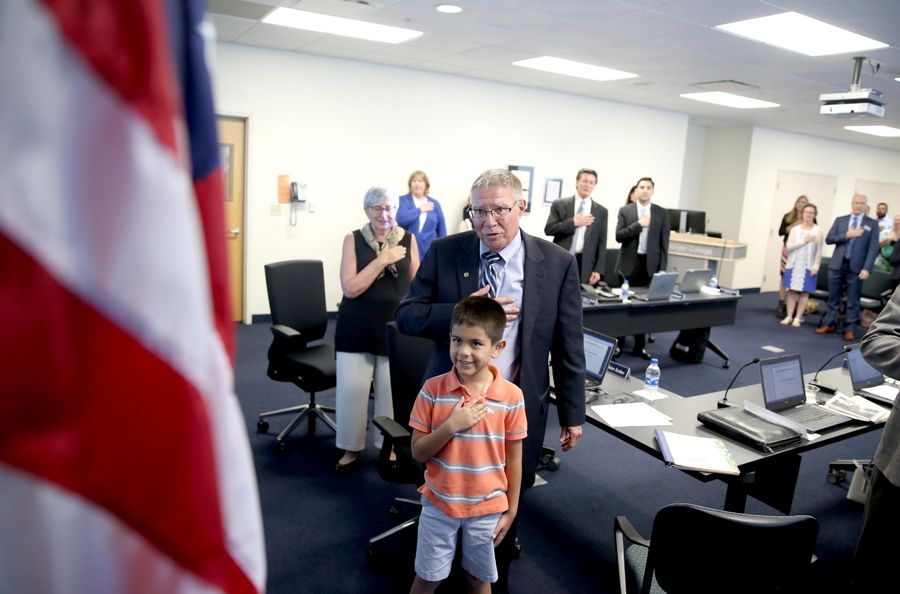 Grandson Shaun Mack, 9, joins outgoing Harper College President Ken Ender for the Pledge of Allegiance on Wednesday night at Ender's final board meeting at the Palatine-based school.