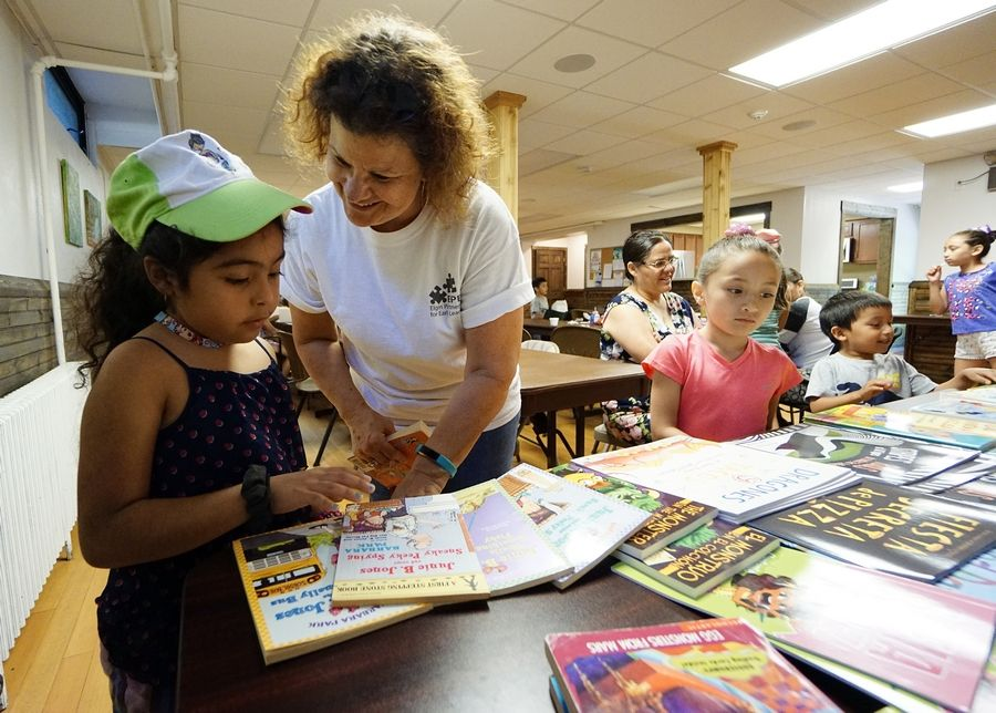 Kris Young from the YWCA helps Nadaly Vriostegvi, 6, of Elgin pick out a book during a free summer lunch program at Izaak Walton Center in Elgin. Data show that statewide only 26% of students entering kindergarten are developmentally ready, according to a state report, so school districts are working on ways to help.