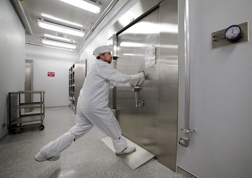 Jeremy Kent, Apollo sample curation processor, tugs to open the 1978 U.S. federal bank vault that protects the entrance to the lunar sample vault inside the lunar lab at the NASA Johnson Space Center Monday, June 17, 2019, in Houston. The door requires two separate combinations, held by two separate people, to open.