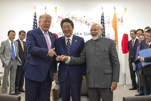 U.S. President Donald Trump, left, jokes to the media about fist bumping with  Japanese Prime Minister Shinzo Abe, center, and Indian Prime Minister Narendra Modi during a trilateral meeting on the sidelines of the G-20 summit in Osaka, western Japan, Friday, June 28, 2019. (Carl Court/Pool Photo via AP)