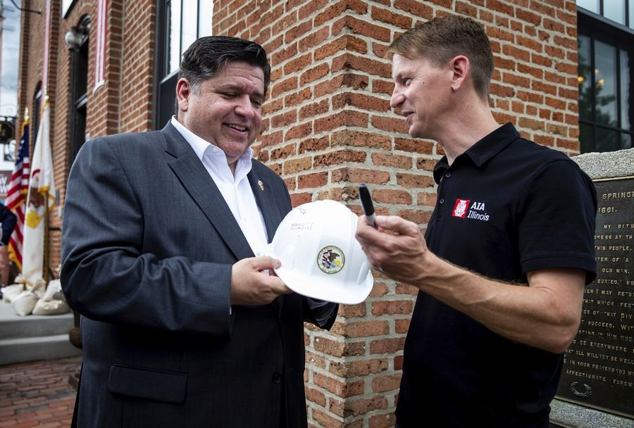 Gov. J.B. Pritzker signs a hard hat for Mike Waldinger, the executive vice president of the American Institute of Architects in Illinois, after the governor signed into law a massive expansion of gambling in Illinois and a $45 billion construction and infrastructure plan during a ceremony at the Lincoln Depot, Friday in Springfield.