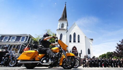 Members of the Jarheads Motorcycle Club pass police honor guards as they roll up to the funeral for Michael Ferazzi at St. Peter's Catholic Church in Plymouth, Mass., Friday, June 28, 2019. Ferazzi, a motorcyclist and retired police officer, was killed in a fiery crash that claimed the lives of seven people riding with the Jarheads Motorcycle Club in New Hampshire.