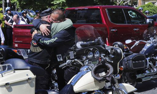 Members of the Jarheads Motorcycle Club embrace prior to the funeral for Michael Ferazzi at St. Peter's Catholic Church in Plymouth, Mass., Friday, June 28, 2019. Ferazzi, a motorcyclist and retired police officer, was killed in a fiery crash that claimed the lives of seven people riding with the Jarheads Motorcycle Club in New Hampshire.