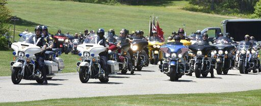 Scores of motorcycle riders follow the hearse to the gravesite at the National Cemetery in Bourne where Marine Corps veteran Michael Ferazzi was buried on Friday, June 28, 2019. Ferazzi was one of 7 killed in a motorcycle accident last weekend in New Hampshire. (Steve Heaslip/The Cape Cod Times via AP)