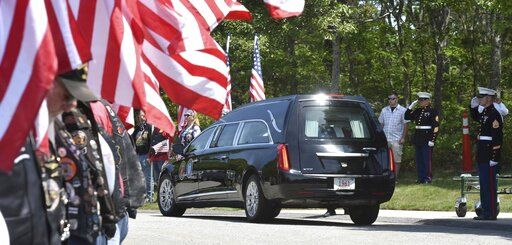 Members of the Patriot Guard Riders line the roadway as the hearse arrives at the National Cemetery in Bourne where Marine Corps veteran Michael Ferazzi was buried on Friday, June 28, 2019. Ferazzi was one of 7 killed in a motorcycle accident last weekend in New Hampshire. (Steve Heaslip/The Cape Cod Times via AP)