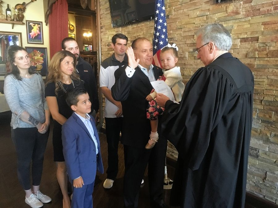 Cook County Judge John Mulroe, right, swears in Rosemont Mayor Brad Stephens, with raised hand, as Illinois state representative for the 20th District, while Stephens' family looks on.