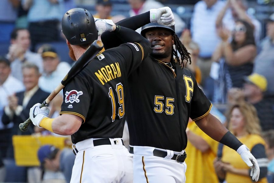 Pittsburgh Pirates' Josh Bell (55) celebrates with Colin Moran (19) as he returns to the dugout after hitting a three-run home run off Chicago Cubs starting pitcher Adbert Alzolay during the first inning of a baseball game in Pittsburgh, Monday, July 1, 2019.
