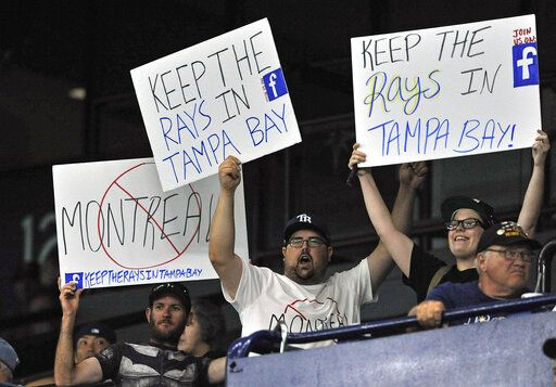 A group of Tampa Bay Rays fans carry signs around the stadium during a baseball game against the Baltimore Orioles Monday, July 1, 2019, in St. Petersburg, Fla.