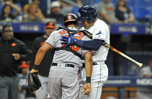 Tampa Bay Rays' Avisail Garcia, right, holds up Baltimore Orioles catcher Pedro Severino, left, after Severino was hit by a foul ball into his shoulder during the third inning of a baseball game Monday, July 1, 2019, in St. Petersburg, Fla.