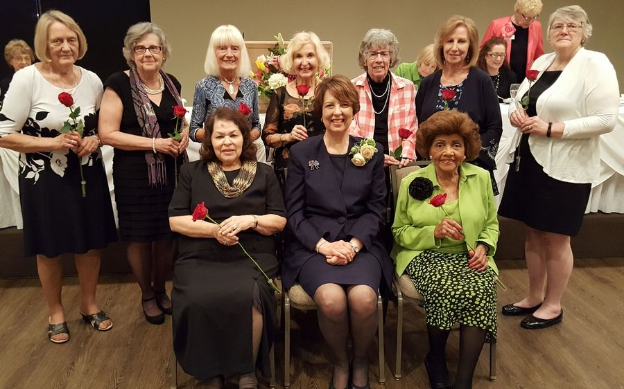Gwen Gage, seated, center, is honored as the 70th annual Woman of the Year. Former award recipients in attendance were also acknowledged with a stemmed rose including: seated, from left, Mary Camacho and Betty Brown; and back row, Sandy Ziros, Marge Haefliger, Nancy Schueneman, Murna Hansemann, Phyllis Blizzard, Karen Fox and Dr. Christine Mueller.